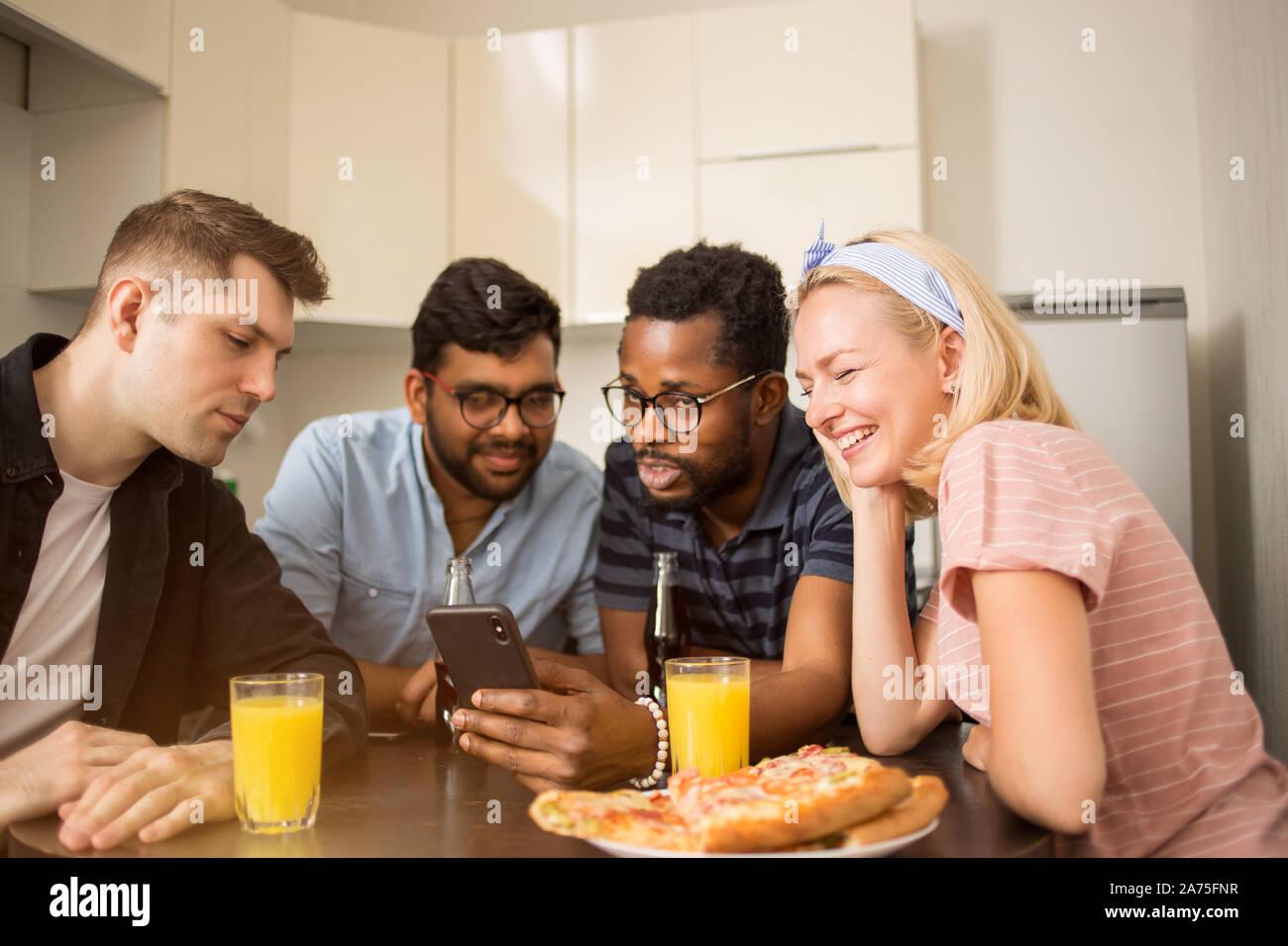 Cuatro amigos sentados a la mesa, comer pizza, beber bebidas gaseosas, la lectura de un mensaje de texto en el teléfono inteligente, prueba nueva aplicación teléfono juntos. Mult Foto de stock