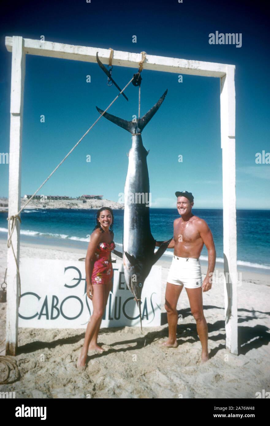 BAJA CALIFORNIA, MÉXICO - JUNIO DE 1962: el actor y ex jugador de béisbol Chuck Connors (1921-1992) y la actriz prometido Kamala Devi (1934-2010), posan para una fotografía delante de un marlin que Connors capturado mientras estaba en un viaje de pesca alrededor de junio de 1962, en Baja California, México. (Foto por Hy Peskin) (número de registro: X8569) Foto de stock