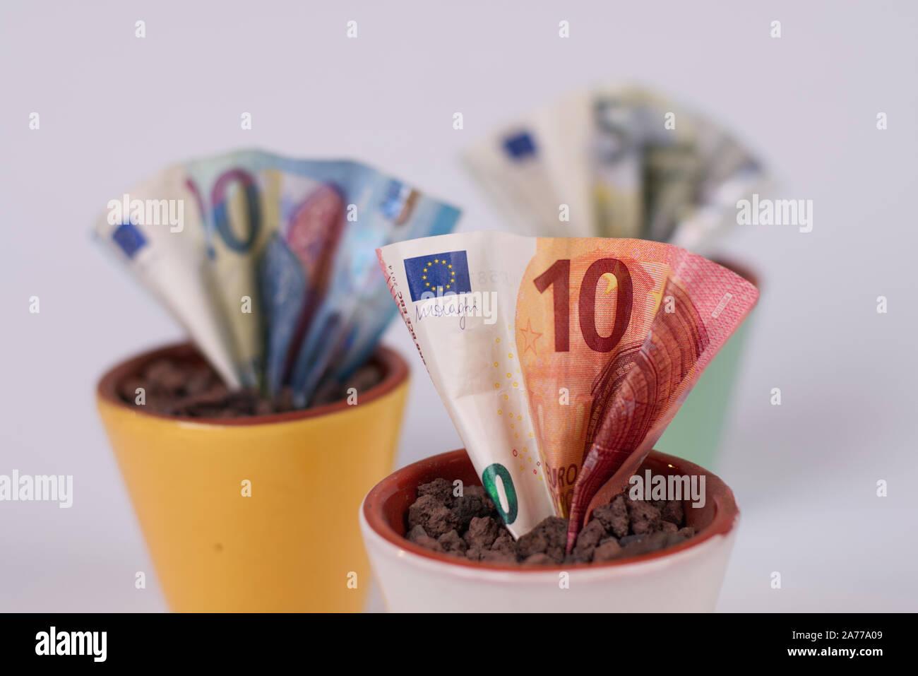 Cómo hacerse rico rápidamente? Simpel: Planta algunos billetes, seriamente, invirtiendo su euro's es una idea mejor. Estas ollas de dinero simboliza su inversión. Foto de stock