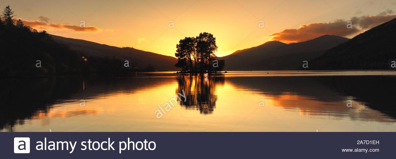 El sol detrás de una isla de árboles de Loch Tay desde Perth y Kinross, Escocia. Foto de stock