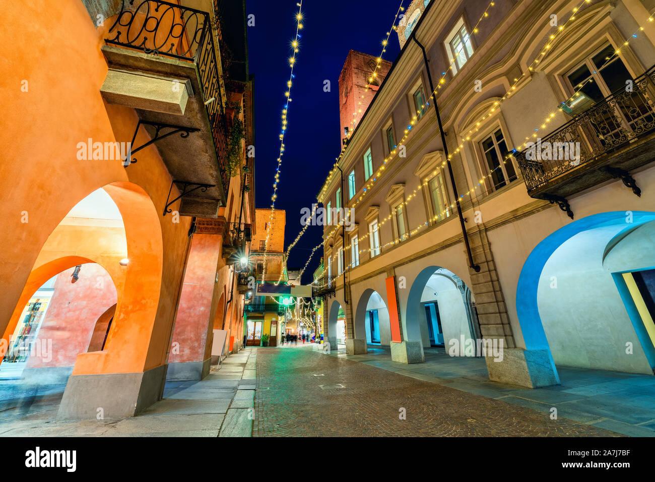 Calle peatonal adoquinada iluminada de noche con las luces de Navidad en el casco antiguo de la ciudad de Alba, Piamonte, Norte de Italia. Foto de stock