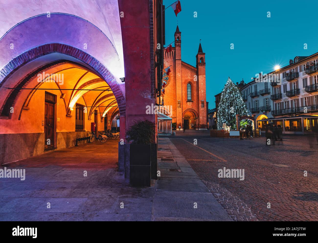Vista de edificios iluminados y árbol de Navidad en la plaza de la ciudad de adoquines en la tarde en la pequeña ciudad de Alba, Piamonte, Norte de Italia. Foto de stock