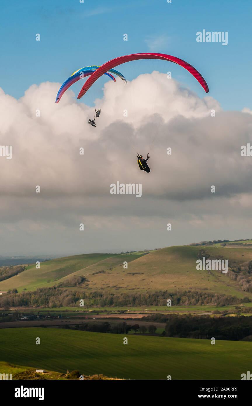 Firle, Lewes, East Sussex, Reino Unido..5 de noviembre de 2019. Un día más brillante que tarde con el viento más frío del norte trae a los pilotos de parapente al popular sitio en los Downs del Sur. . Foto de stock