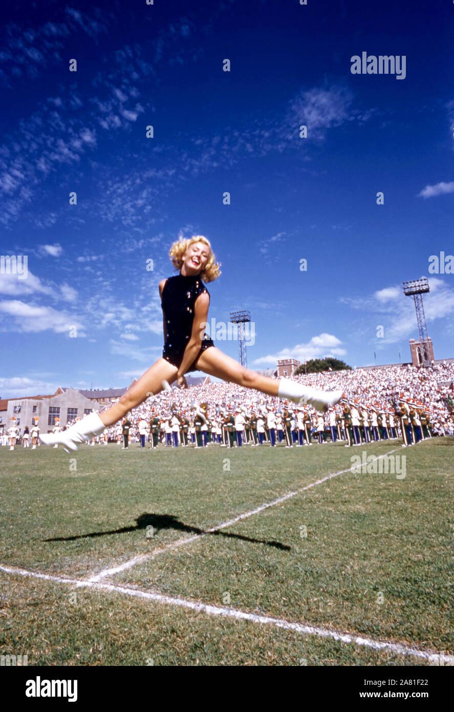ATLANTA, GA - 17 DE SEPTIEMBRE: UNA porra twirler bailes en el campo como los Huracanes de Miami band realiza durante el descanso entre un juego de NCAA con los Huracanes de Miami y Georgia Tech Yellow Jackets, el 17 de septiembre de 1955 en el Grant Field en la ciudad de Atlanta, Georgia. Los Yellow Jackets derrotaron a los huracanes 14-6. (Foto por Hy Peskin) (número de registro: X3090) Foto de stock
