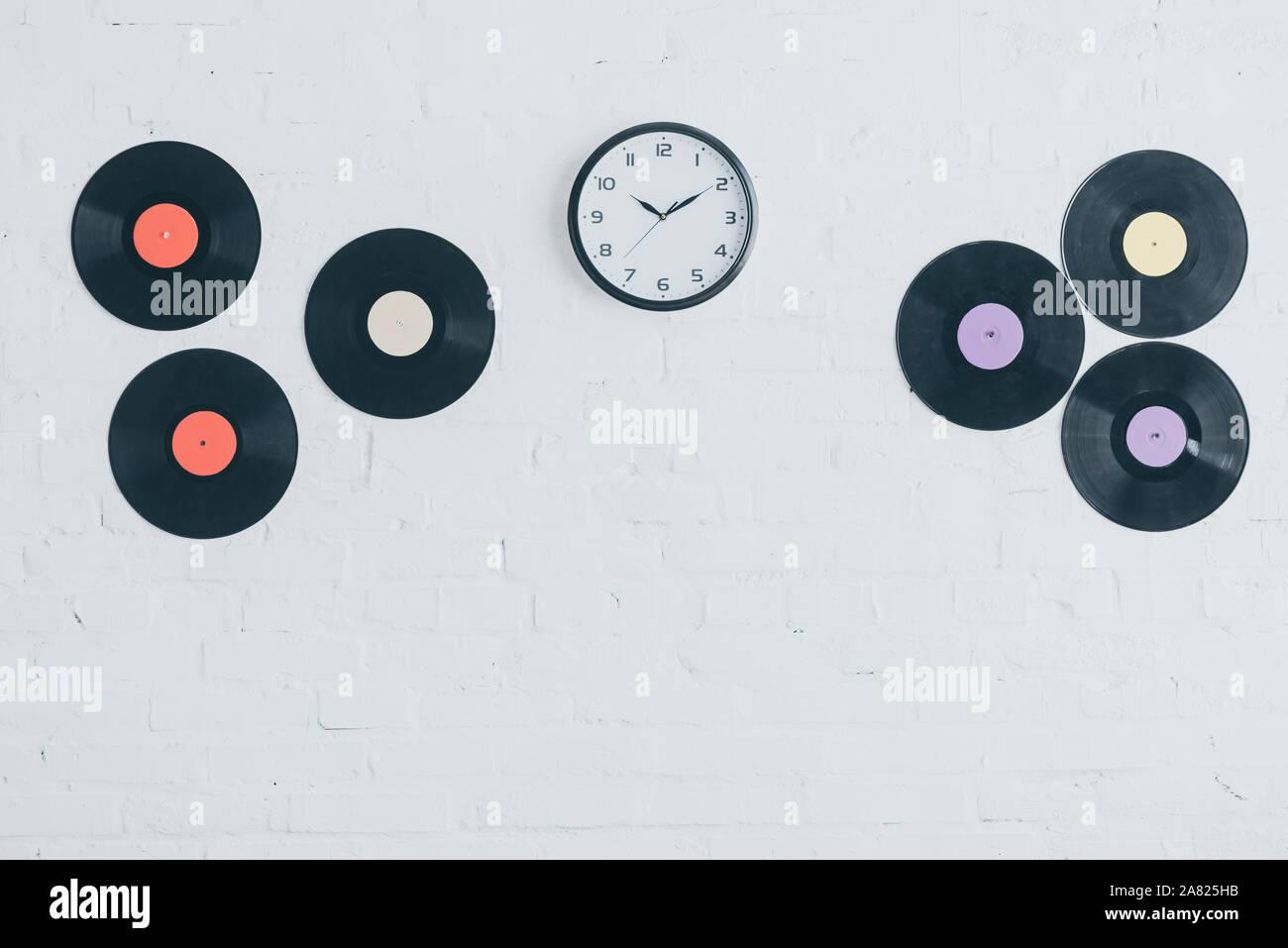 Los discos de vinilo y redondo reloj de pared de ladrillo blanco. Foto de stock