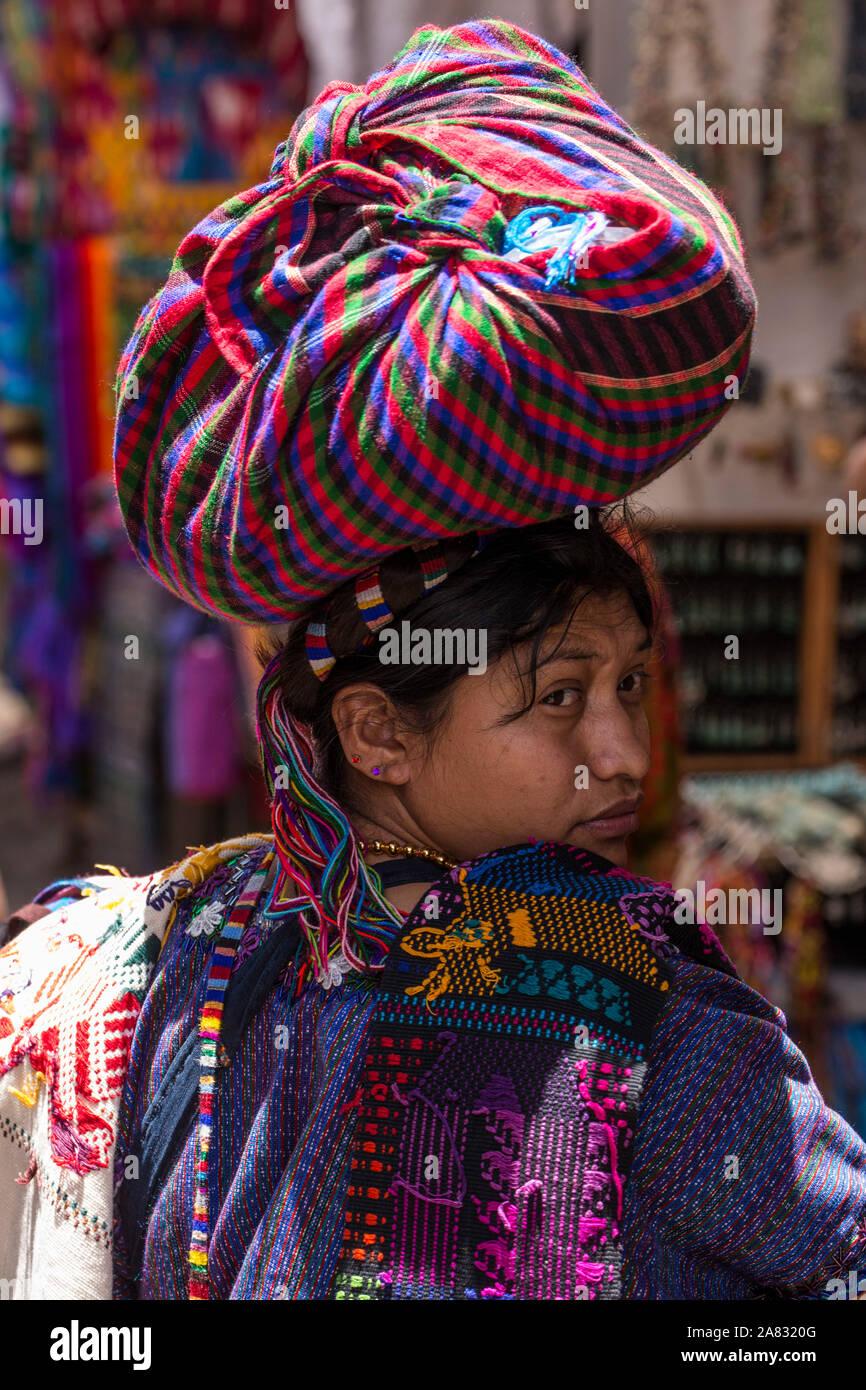 Joven cantó Antonio Palopó en el mercado de Chichicastenango, Guatemala llevar sus bienes en su cabeza, mirando hacia atrás sobre su hombro. Ella Foto de stock