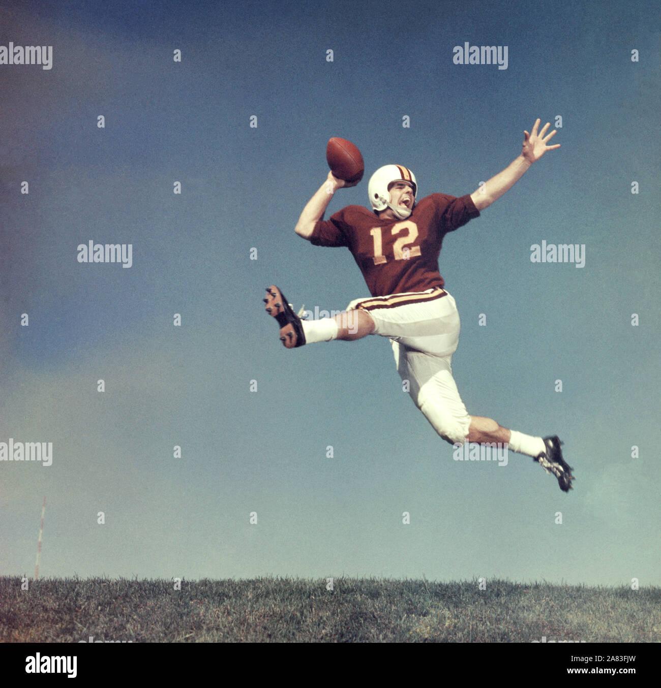 Jugadores de fútbol americano no identificado 1950 saltar en el aire con el balón (Foto por Hy Peskin) Foto de stock