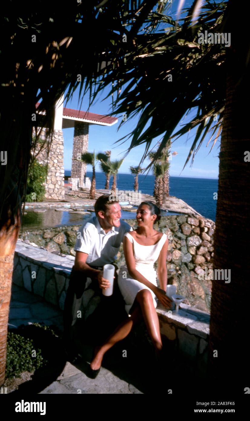BAJA CALIFORNIA, MÉXICO - JUNIO DE 1962: el actor y ex jugador de béisbol Chuck Connors (1921-1992) y la actriz prometido Kamala Devi (1934-2010) sentarse fuera en el Cabo San Lucas Hotel durante un viaje de pesca alrededor de junio de 1962, en Baja California, México. (Foto por Hy Peskin/Getty Images) (número de registro: X8569) *** Local Caption *** Kamala Devi;Chuck Connors Foto de stock