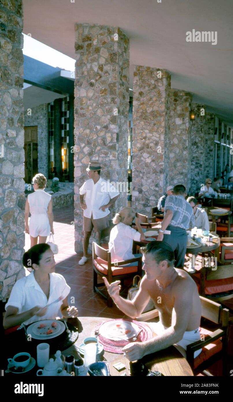 BAJA CALIFORNIA, MÉXICO - JUNIO DE 1962: el actor y ex jugador de béisbol Chuck Connors (1921-1992) y la actriz prometido Kamala Devi (1934-2010) desayunar afuera en el Cabo San Lucas Hotel durante un viaje de pesca alrededor de junio de 1962, en Baja California, México. (Foto por Hy Peskin) (número de registro: X8569) *** Local Caption *** Kamala Devi;Chuck Connors Foto de stock
