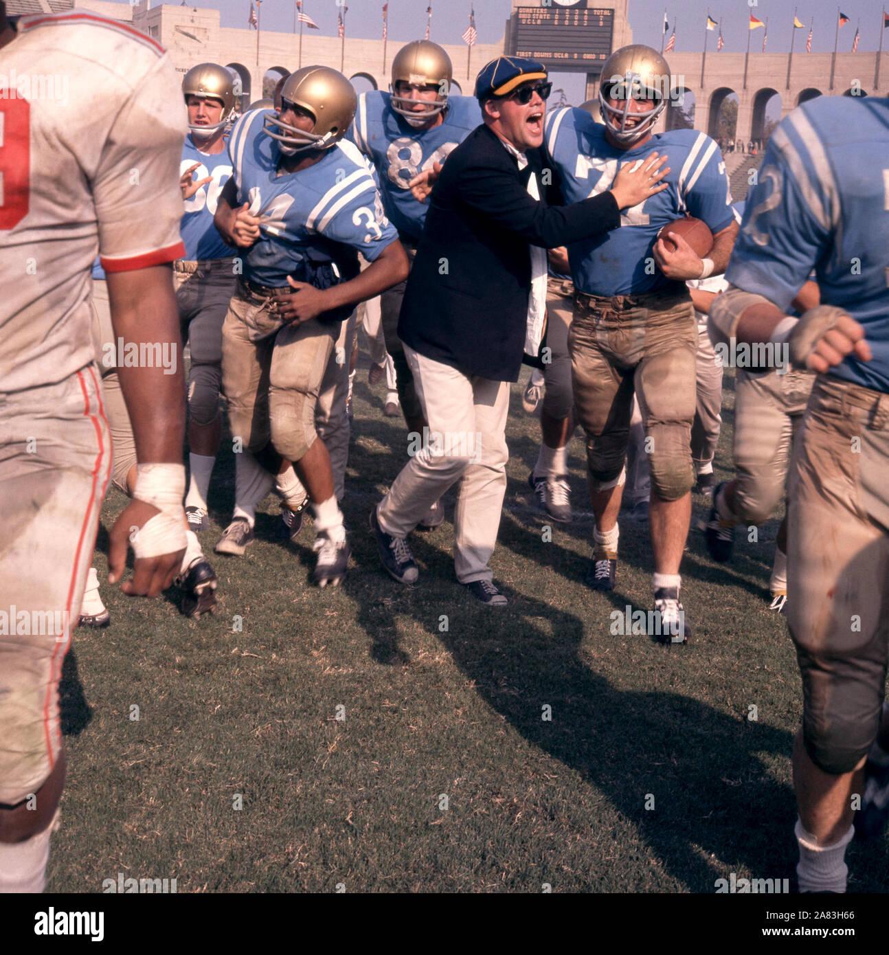 LOS ANGELES, CA - 6 de octubre: Warren Jackson #34 y Phil Oram #77 de la UCLA Bruins celebrar con un ventilador tras derrotar a los Ohio State Buckeyes después de un partido de NCAA en Octubre 6, 1962 en el Los Angeles Memorial Coliseum en Los Angeles, California. (Foto por Hy Peskin) (número de registro: X8760) *** Local Caption *** Warren Jackson;Phil Oram Foto de stock