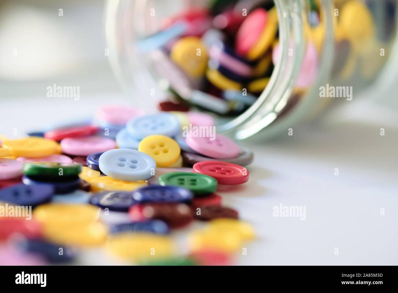 Gran grupo de coloridos cosiendo botones de plástico en una lata en la mesa, con espacio para copiar texto Foto de stock