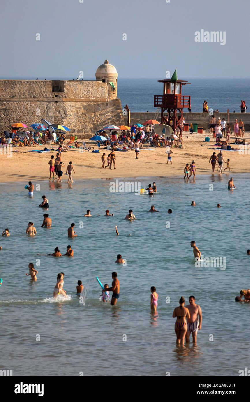 Vistas de la bulliciosa playa La Caleta en una soleada tarde de verano, Cádiz, Andalucía, España, Europa Foto de stock