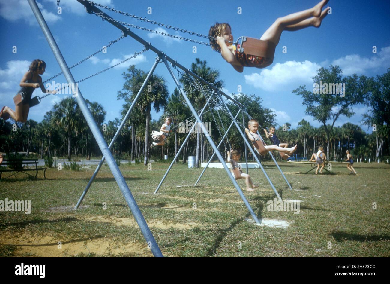 1954: Los niños swing en un columpio en su patio de recreo en 1954. (Foto por Hy Peskin) Foto de stock