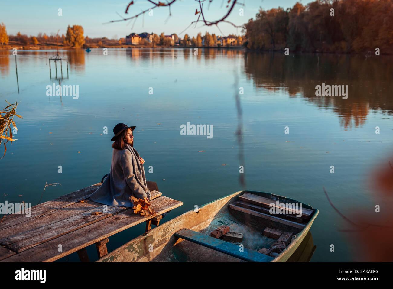 Mujer sentada sobre el lago de pier por barco admirando el paisaje de otoño y relajante. Temporada de otoño actividades Foto de stock