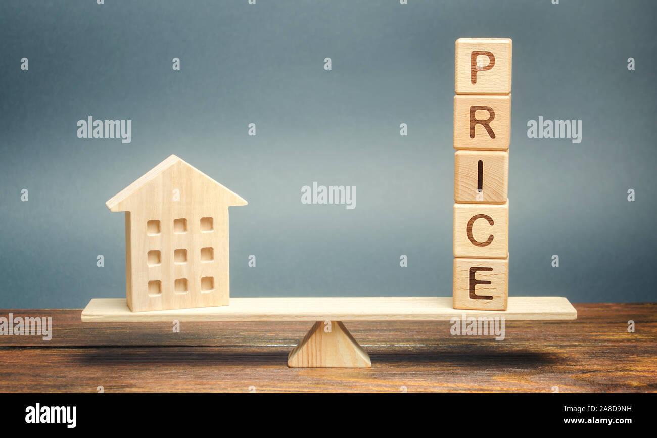 Casa de madera y la palabra en las escalas de precios. Concepto de propiedad de valoración justa. Inicio evaluación. El comercio justo y el costo. Legal transparente. Business Foto de stock