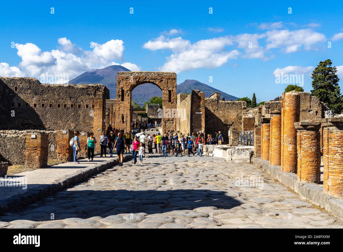Vista de la via del Foro en la antigua ciudad de Pompeya con el arco de Calígula y el Monte Vesubio en el fondo. Pompeya, Italia, en octubre de 2019 Foto de stock