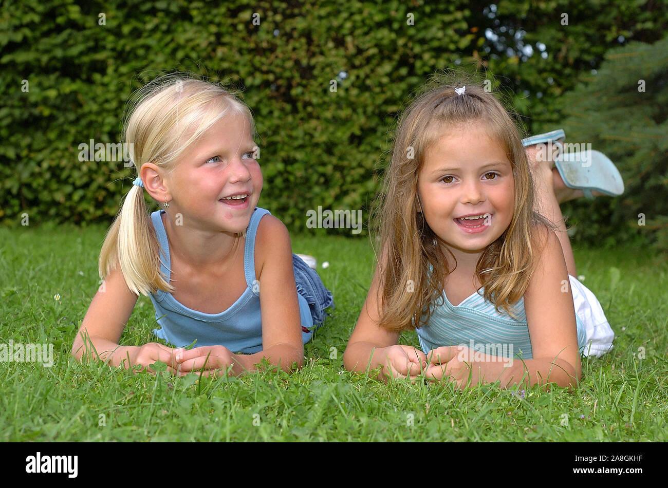 Zwei lachende Kinder liegen im Park auf einer Wiese, Mädchen, 6 Jahre, señor: Sí Foto de stock