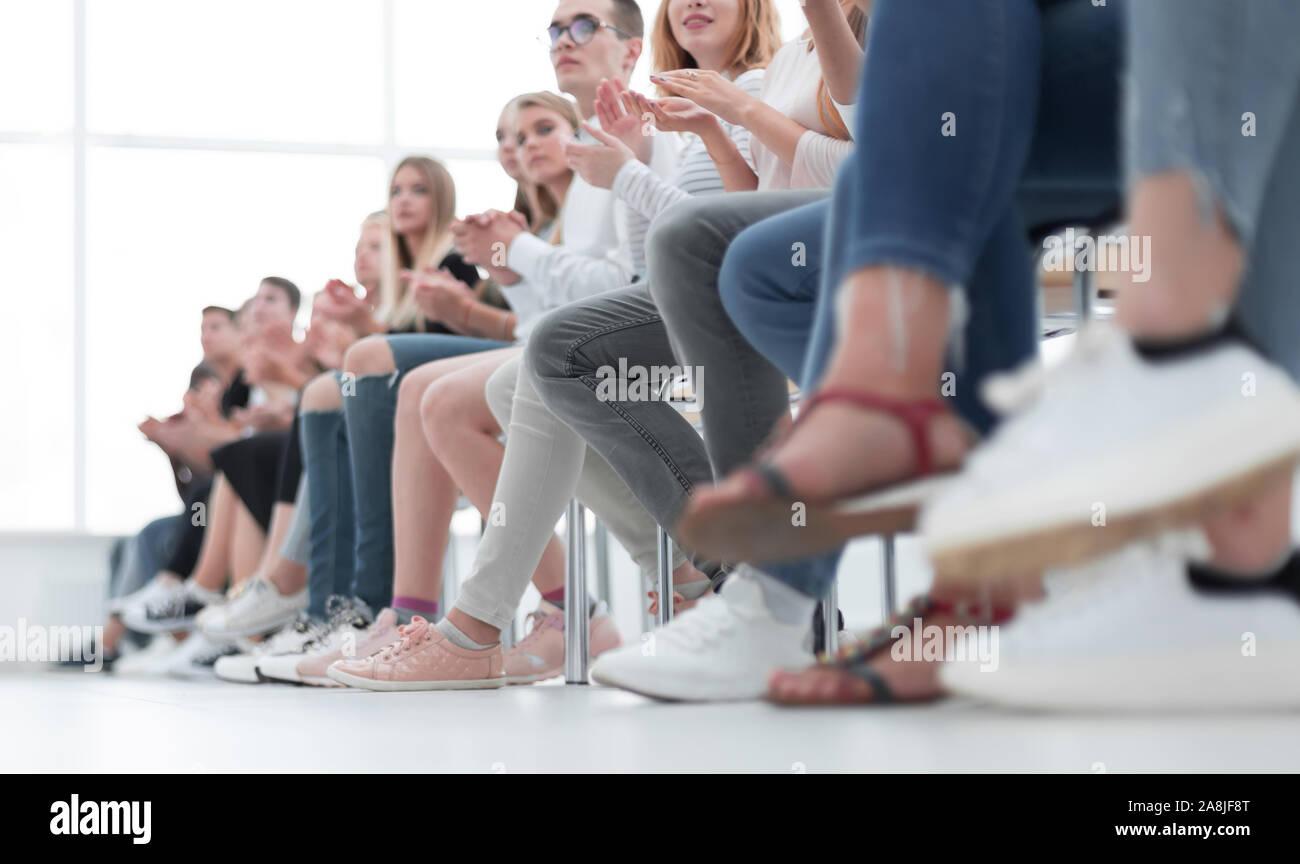 Grupo de diversos jóvenes sentados en una fila Foto de stock