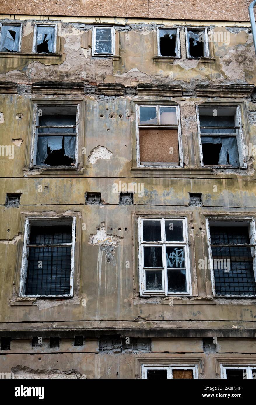 Antigua Casa desolada con daños en la fachada y ventanas Bursted Foto de stock