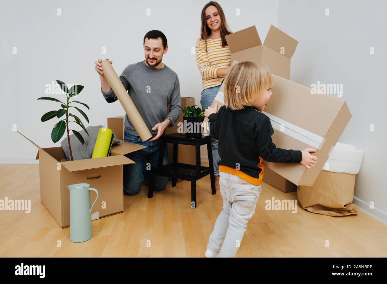 Joven familia se mudó a una nueva casa, desembalaje de cajas de cartón junto Foto de stock