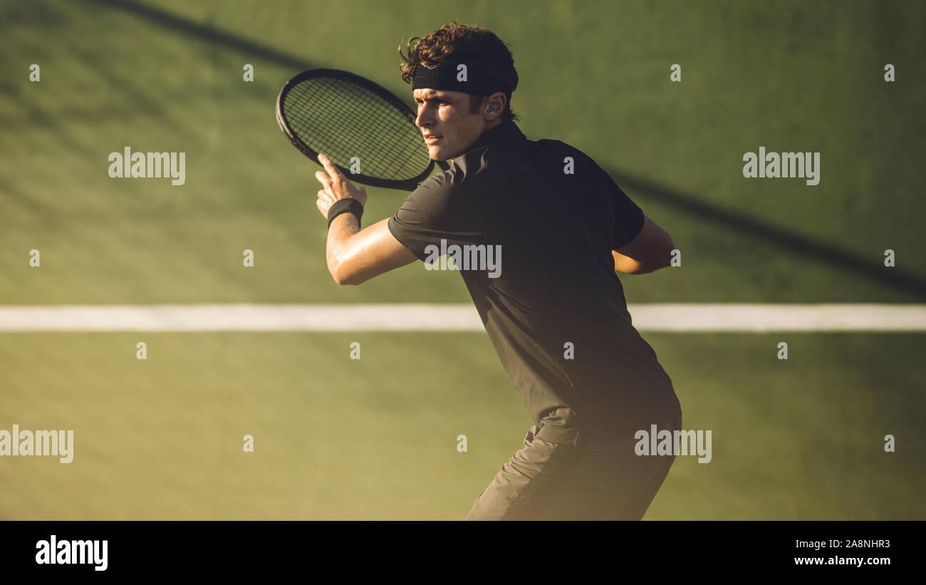 Los jugadores jóvenes a jugar al tenis en la pista dura. Golpear a un jugador de tenis profesional forehand durante un partido. Foto de stock
