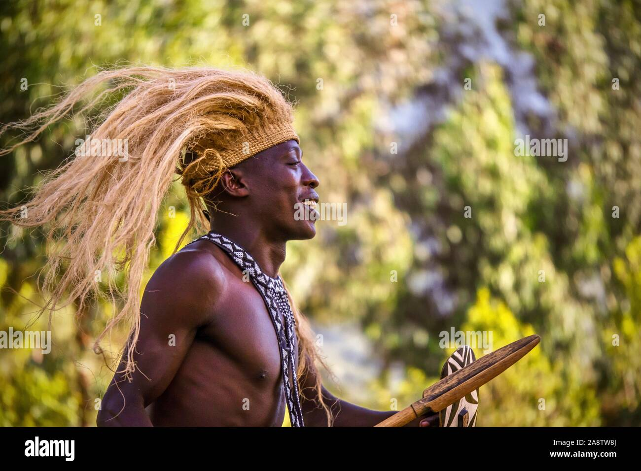 Parque Nacional de Los Volcanes (Rwanda) - Septiembre 20, 2015: Un hombre joven ruandesa está realizando una danza cultural para turistas, vistiendo un tradicional tribal h Foto de stock