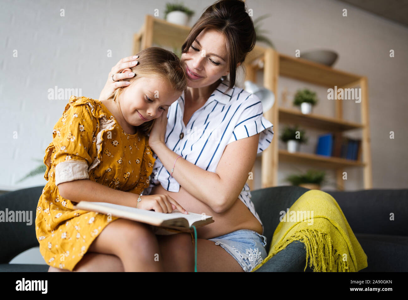 Retrato de la madre embarazada y su hija leyendo un libro en el salón Foto de stock