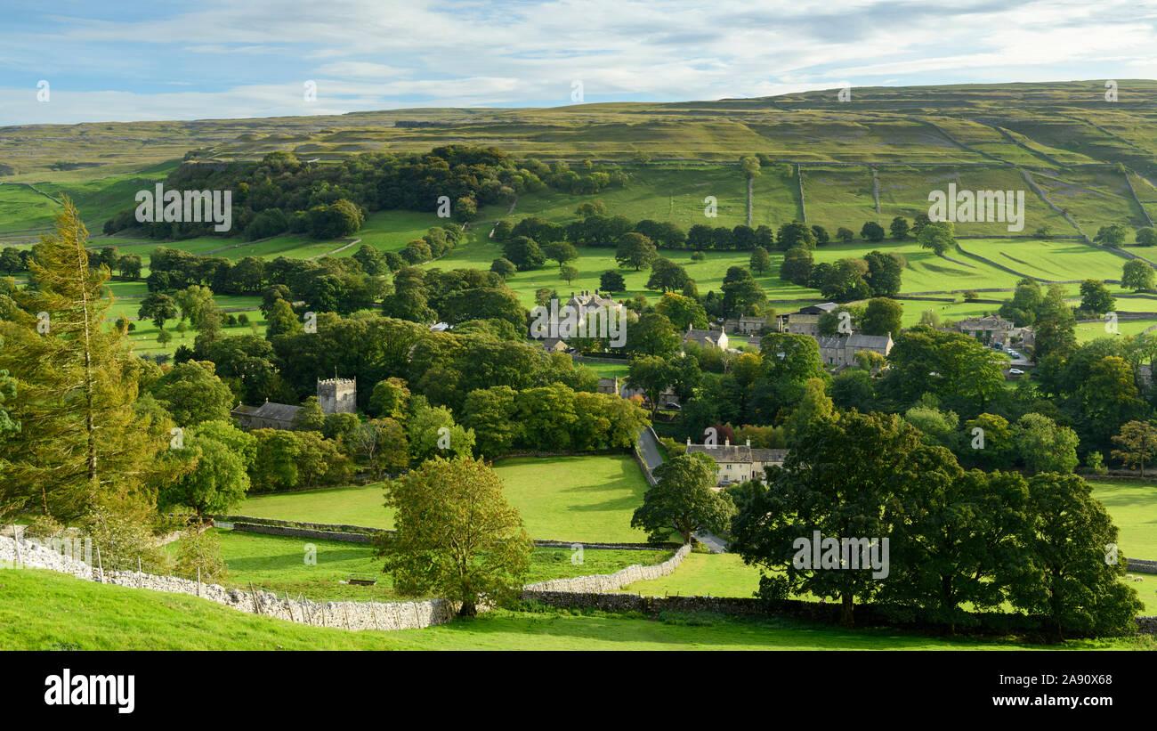 Noches de verano, la luz solar en la pintoresca aldea de Dales (iglesia y casas) anidando en el valle bajo altas colinas - Arncliffe, North Yorkshire, Inglaterra, Reino Unido. Foto de stock