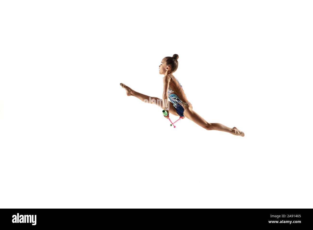 Little Girl flexible aislado sobre fondo blanco studio. Poco modelo femenino como una gimnasia rítmica en brillante artista leotard. Gracia en el movimiento, la acción y el deporte. Hacer ejercicios con las mazas. Foto de stock