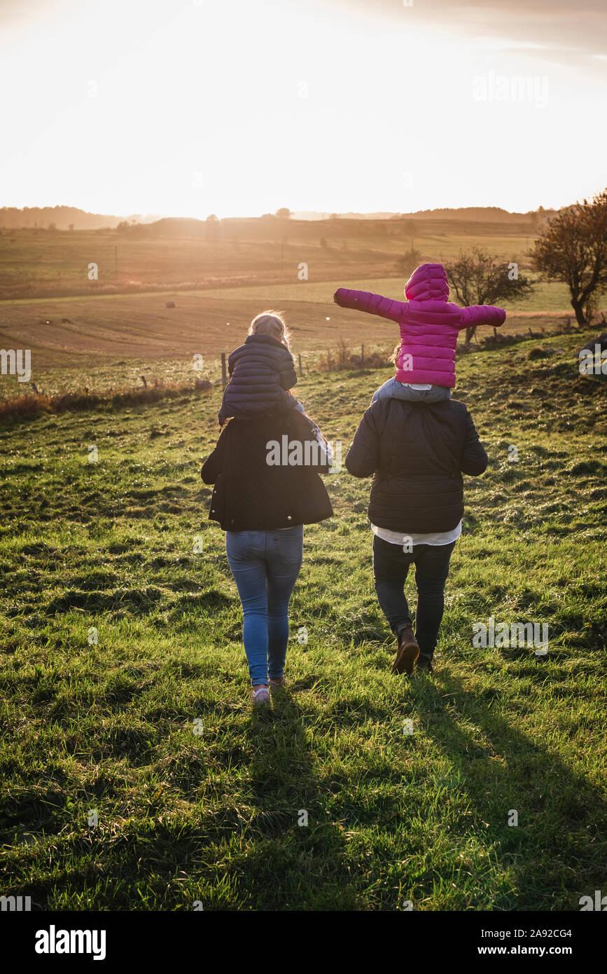 Familia caminar sobre la pradera Foto de stock