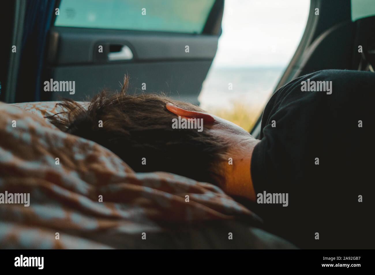 Persona durmiendo en el coche Foto de stock