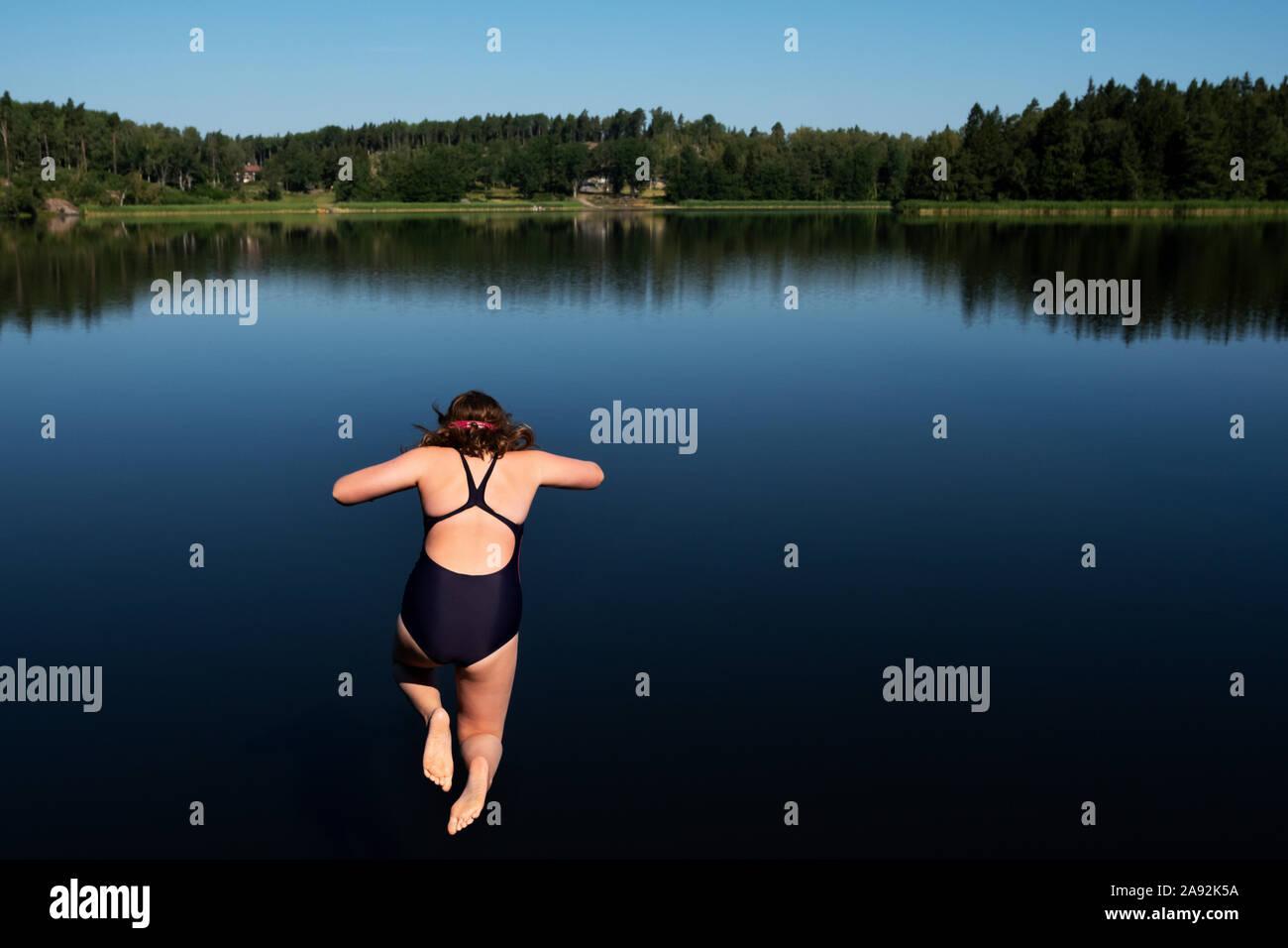 Chica saltar en el lago Foto de stock