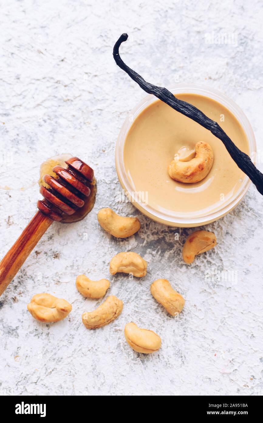 Nuez de mantequilla en el vidrio. Materias orgánicas caseras anacardos pegar sobre fondo gris con la miel y la vainilla. Concepto de alimentos naturales saludables. Vista desde arriba. Foto de stock