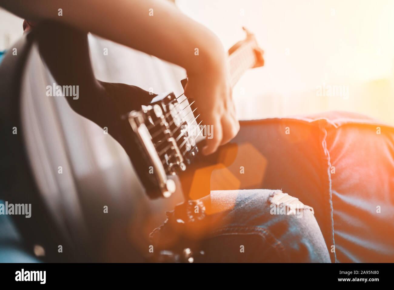 Primer plano de un niño tocando una guitarra eléctrica negra - la mano golpea las cuerdas Foto de stock