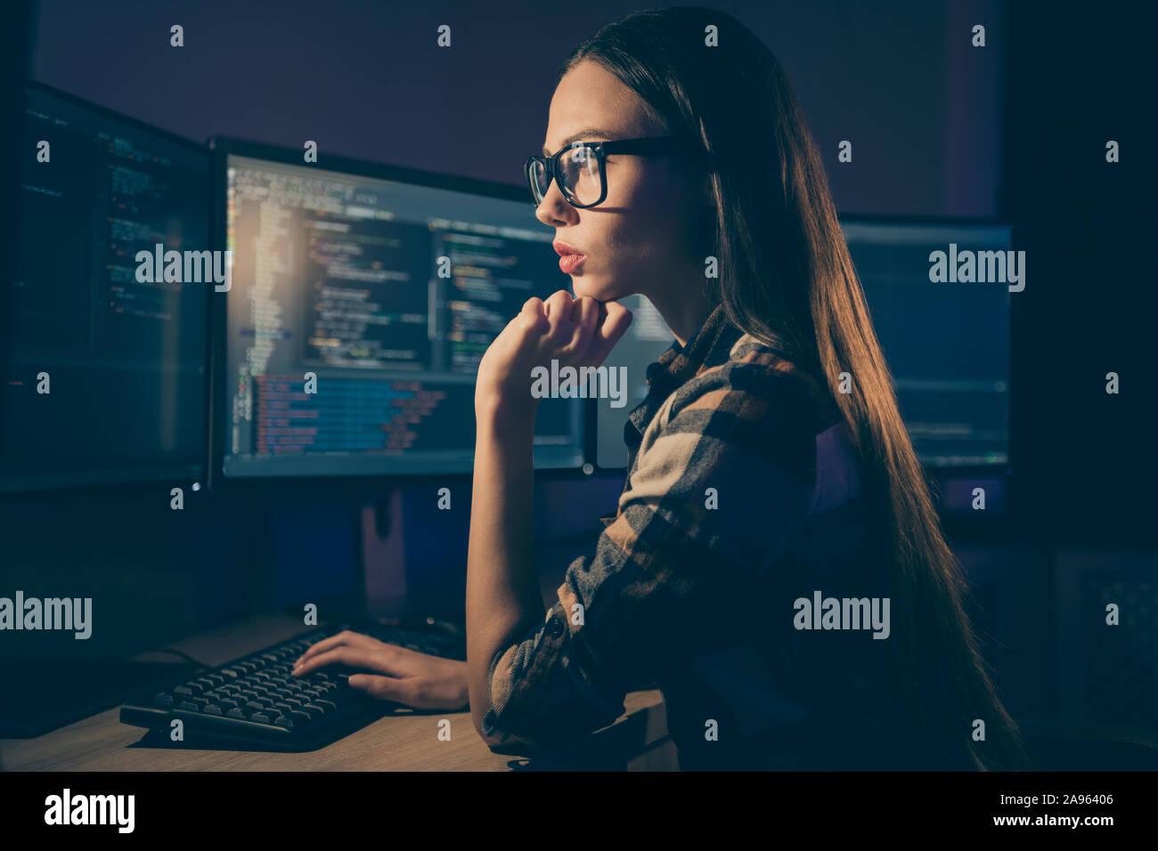 El perfil lateral foto de adivinar el pensamiento inteligente mujer que trabaja en el turno nocturno en lugar de su colega, el administrador del sistema Foto de stock