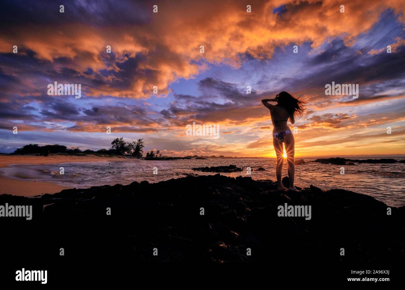 Una joven mujer se detiene para celebrar la puesta de sol sobre la playa Makalawena Hawaii Foto de stock
