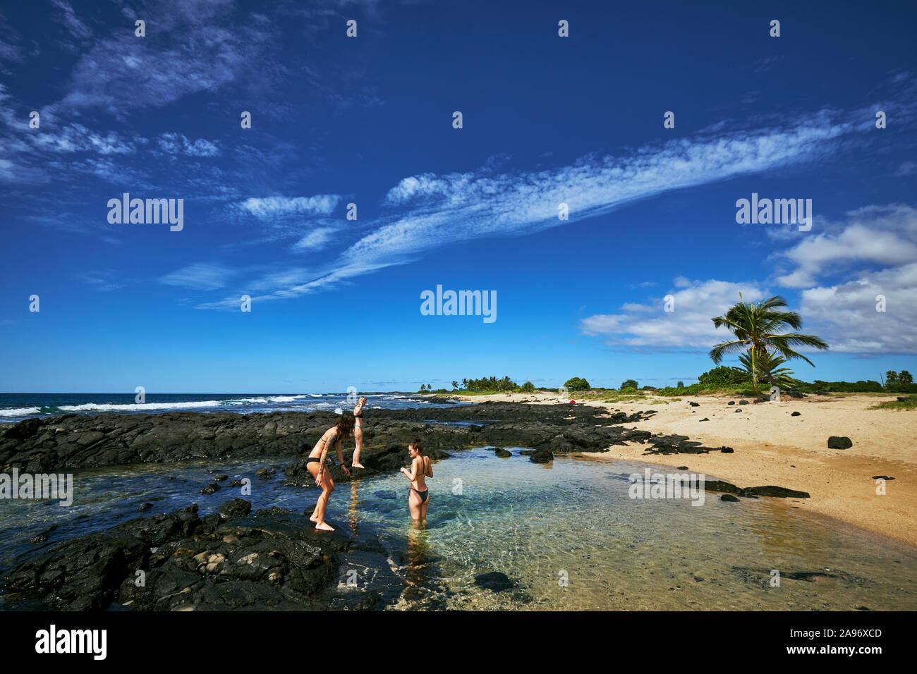 Tres mujeres jugando en una piscina natural en la Isla Grande de Hawai Foto de stock