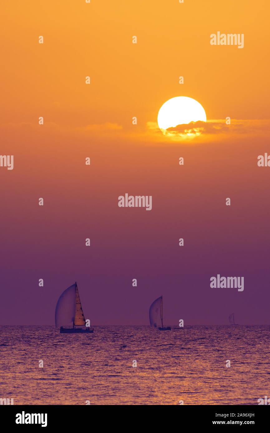 Tres veleros en el mar Adriático con la puesta del sol y las nubes de colores en el fondo Foto de stock