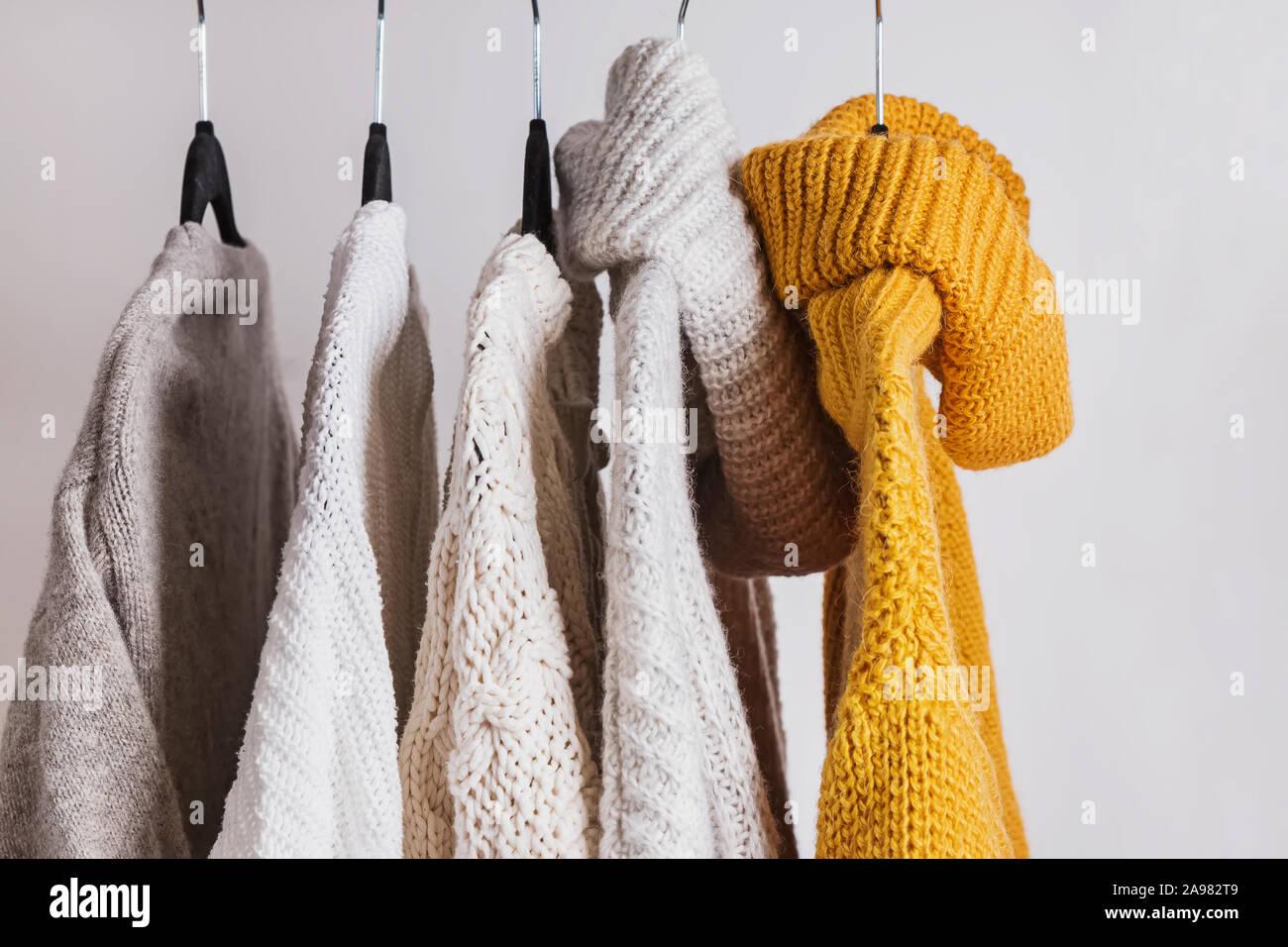 Suéteres tejidos cálidos en las perchas. Foto de stock