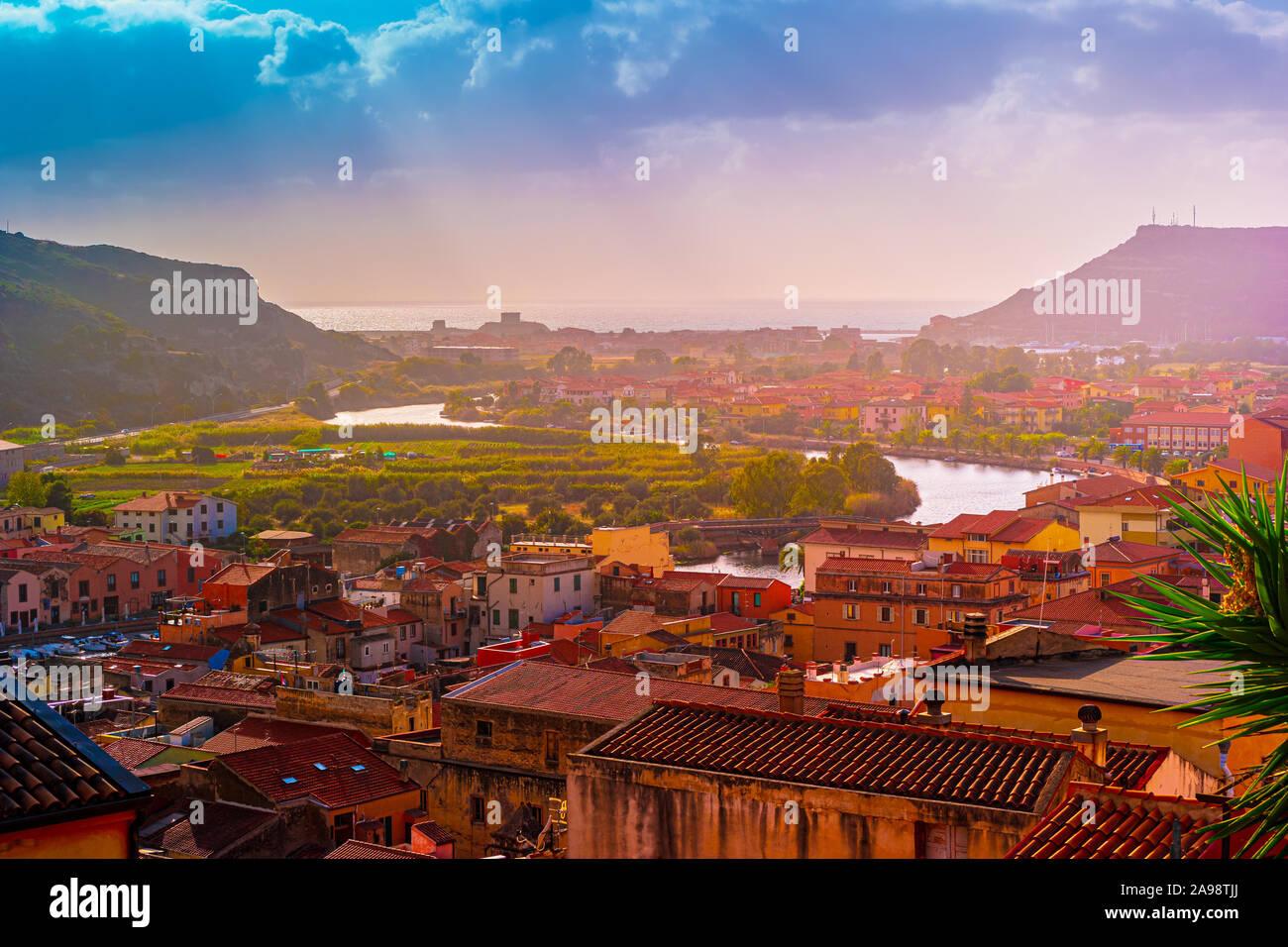 Vista desde arriba en la ciudad de Bosa con casas con tejados rojos, montañas con árboles verdes y el río Temo que fluye hacia el mar Mediterráneo. Ubicación th Foto de stock