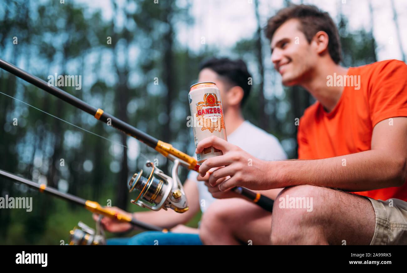 Dos pescadores relajante junto con cerveza, mientras que la pesca en el lago a la mañana Foto de stock