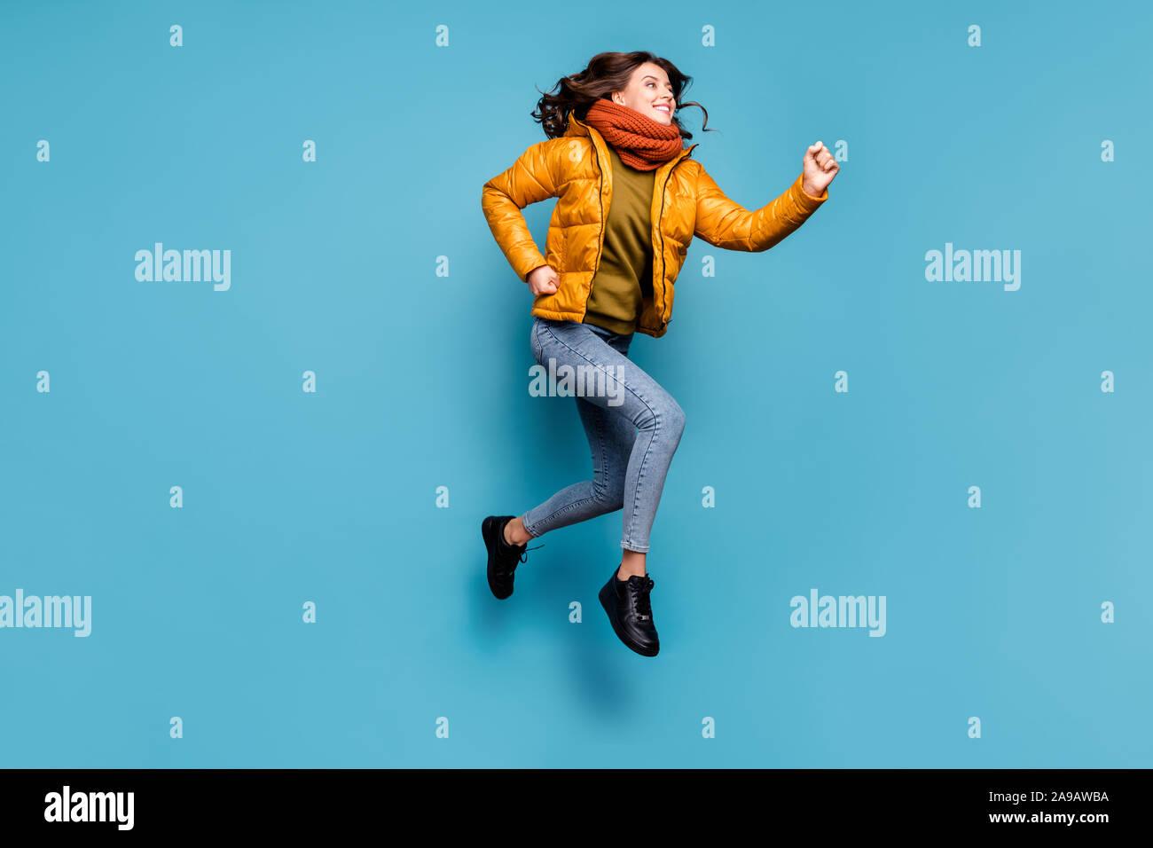 Foto de longitud completa loco dama milenario saltar la velocidad de funcionamiento alta temporada de compras descuentos desgaste Cortavientos elegante bufanda jeans pullover aislado Foto de stock