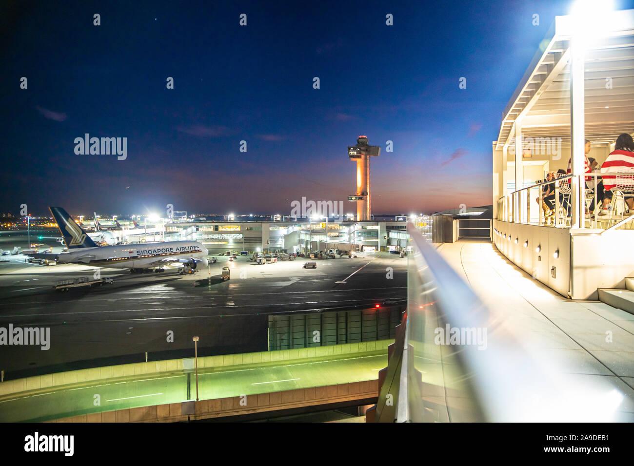 La CIUDAD DE NUEVA YORK - Septiembre 20, 2019: Vista del histórico Hotel TWA y la pista de aterrizaje con aviones visto desde el aeropuerto John F. Kennedy en Queens, Nueva York en la noche Foto de stock