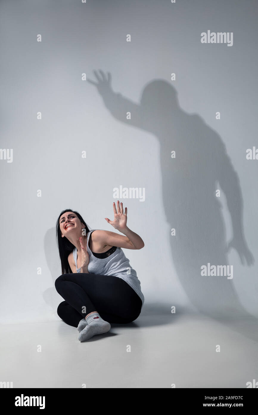 Mujer en el temor de la violencia doméstica, la violencia, el concepto de  los derechos femeninos. Detener agresión. Sombra en la pared que  representan los lados ocultos de abusar, siendo víctima del