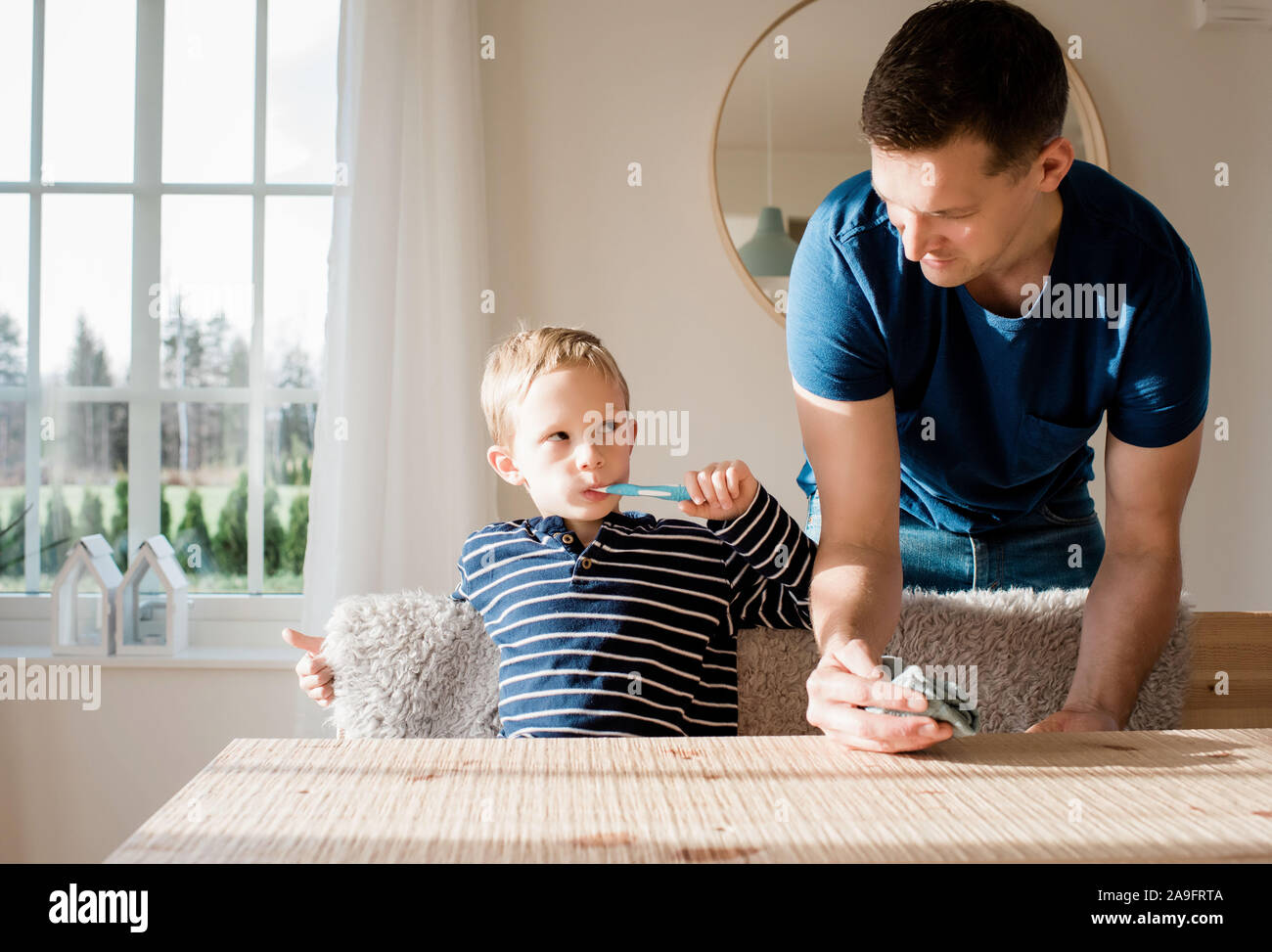 Joven cepillar sus dientes mirando a su papá antes de la escuela Foto de stock