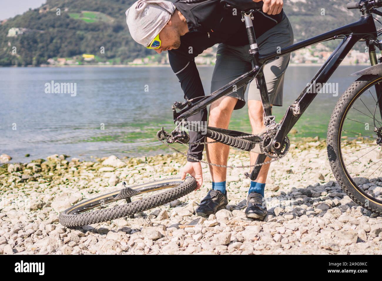 Reparación de bicicletas. Hombre reparando bicicletas de montaña. Ciclista hombre en apuros de rueda trasera caso de accidente. Hombre bicicleta fija cerca del lago en Italia antecedentes Foto de stock