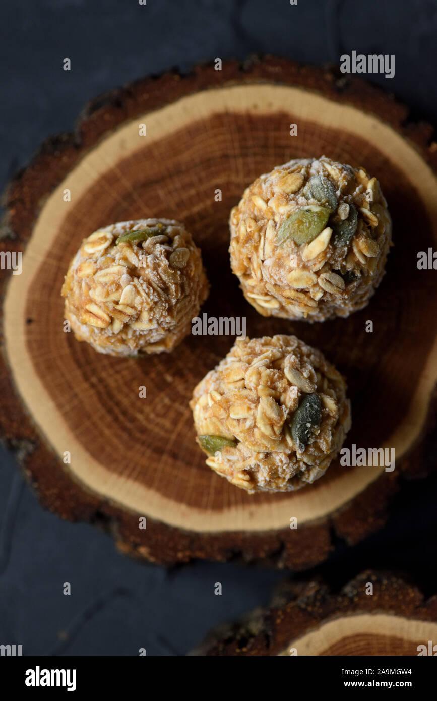 Concepto de comida vegetariana. Cerca de bolas de energía avena congelados con semillas de calabaza sobre losa de madera de roble sobre fondo negro espacio copia de vista superior Foto de stock