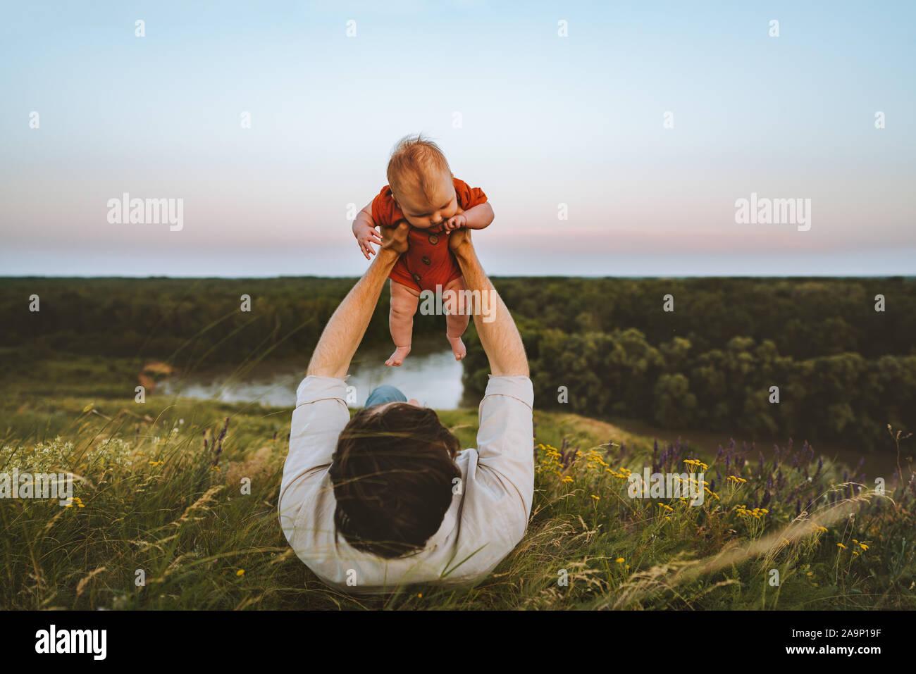 Padre e hija recostada sobre la hierba al aire libre estilo de vida familiar papá y bebé niño caminando juntos las vacaciones de verano la paternidad niñez concepto Foto de stock