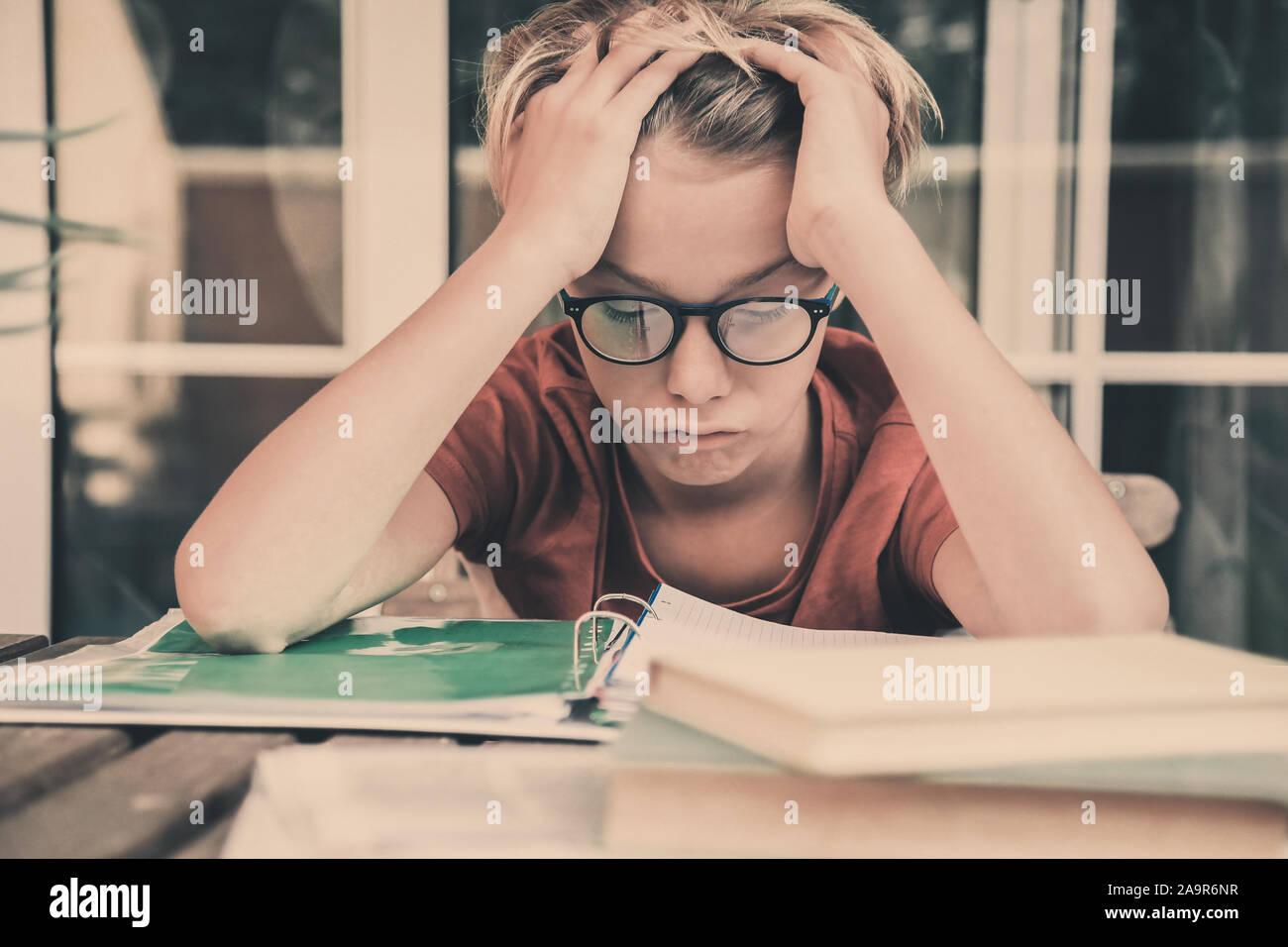 Cansado estudiante haciendo los deberes en casa sentados exterior con libros y periódicos. Chico cansado debido a su gran estudio. Niño dormido en el copybook después l Foto de stock