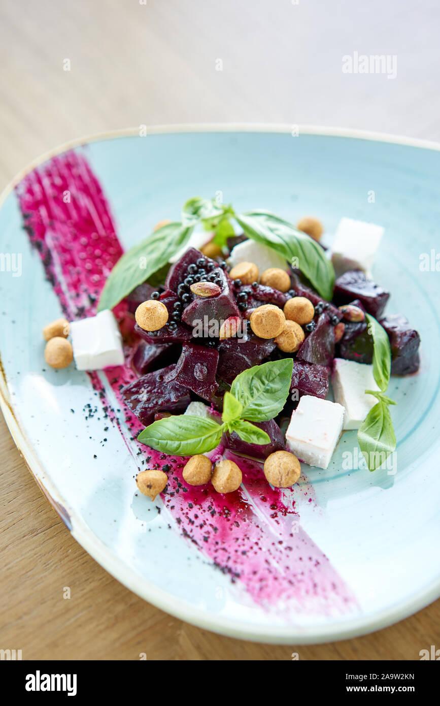 Dieta saludable comida. El italiano con ensalada de remolacha, albahaca y queso feta, con aceite y pequeños profiteroles. Foto de stock